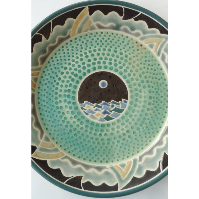 A studio ceramic platter with a striking design including a night sea theme, with central design of a moon over waves and...
