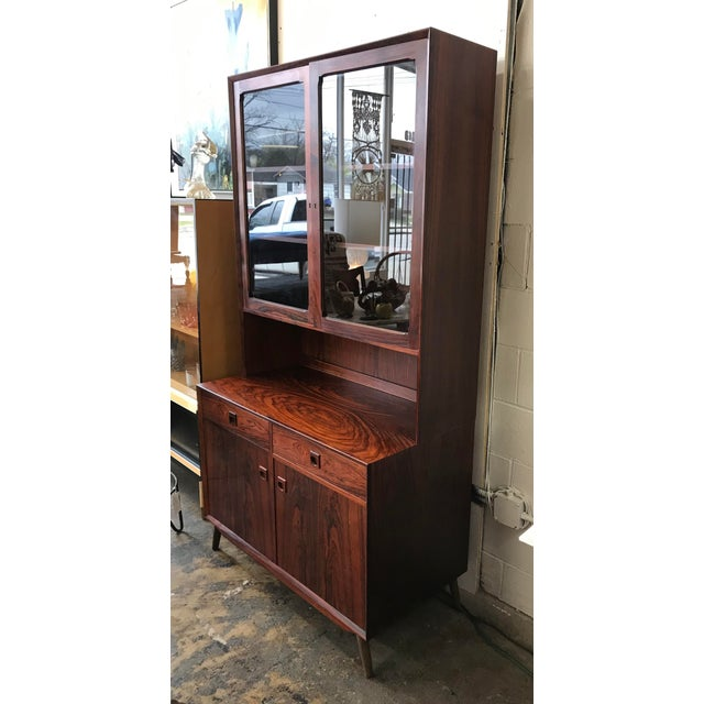 This is a (2) piece all- rosewood cabinet and hutch. The top has glass doors with adjustable shelves. The bottom has (2)...