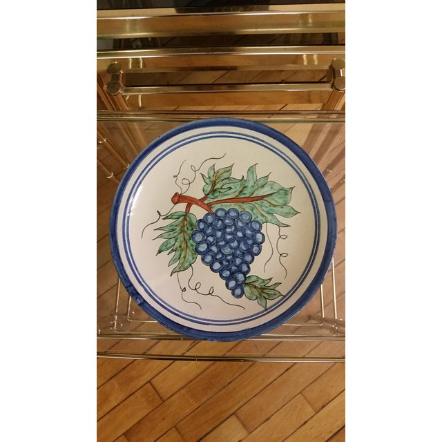 Here's a vintage Mexican redware decorative plate that features grapes. It has holes on backside for hanging on the wall....