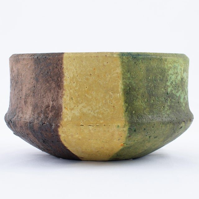 Large ceramic bowl with a highly textured surface finished in matte yellow, green and burgundy glazes, by Italian master...