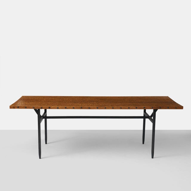 A rectangular dining table by Jean Touret with a hand scraped solid oak top. The edges of the table top are bordered with...