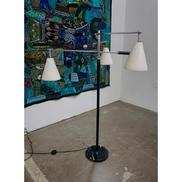 "Stamped ""made in Italy"". 3 armed, articulated, adjustable floor lamp on a black marble base.Chromed arms with white..."