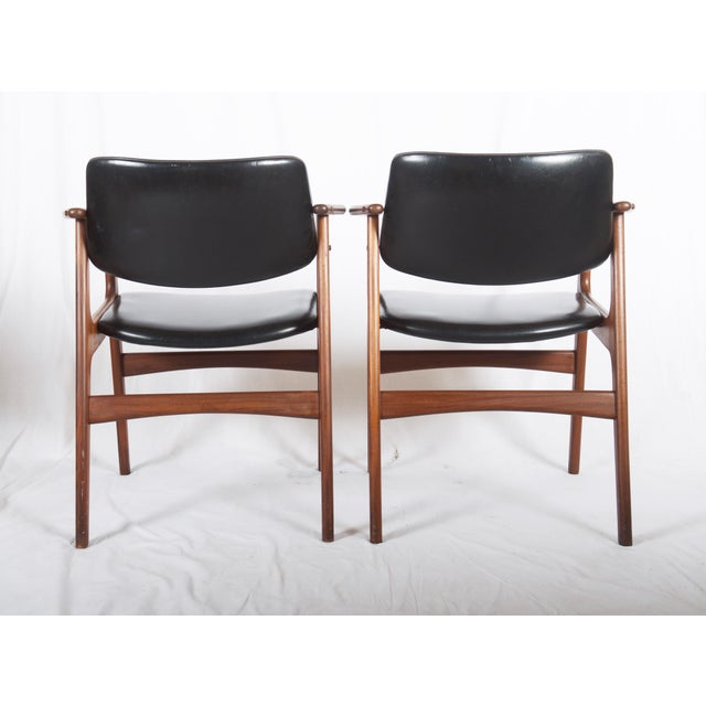 Solid teak frame with upholstered seat and backrest in black leatherette. Made in Denmark in the late 1960s. New...
