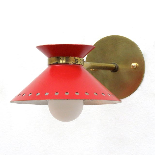 Wonderful pair of red enameled French double cone wall lights by Arlus, with pivoting shades, perforated along the bottom...