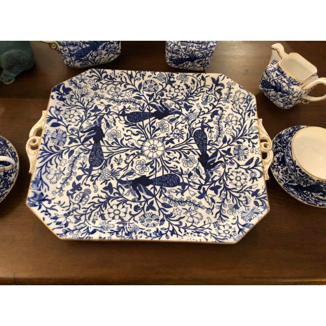 A beautiful blue and white tea set with gold leaf detailing having peacock pattern and including tray, two cups and...