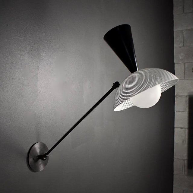 The MOLTO wall-mount reading lamp or wall sconce is a fresh take on Italian modernism, featuring a spun metal mesh shade....