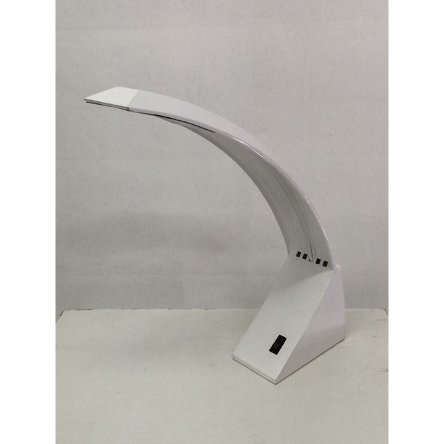 1970s white lacquer desk lamp with sleek aerodynamic shape and curved arm over solid triangular base.
