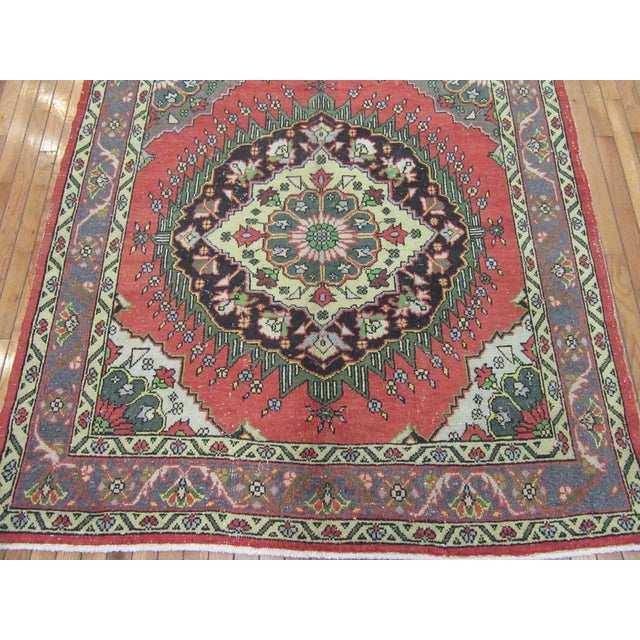 This is a wide and long hand knotted vintage Turkish Anatolian hall runner rug. It is made with wool dyed in primary...