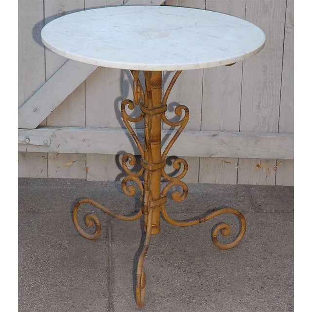 A lovely garden or end table with a marble top on a painted faux bamboo iron work base.