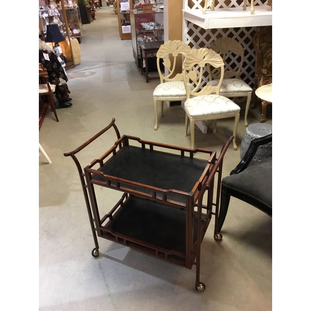 Excellant vintage tea cart in rosewood with a Chinese influence. Top and bottom shelf are black. Casters are in good...