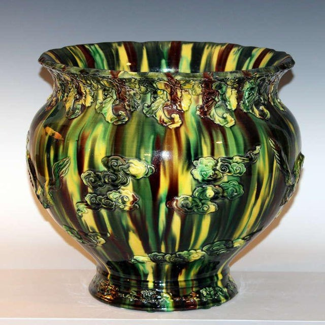 Awaji Pottery jardiniere with applied decoration of dragons amidst clouds and a three color drip glaze, circa 1920s....