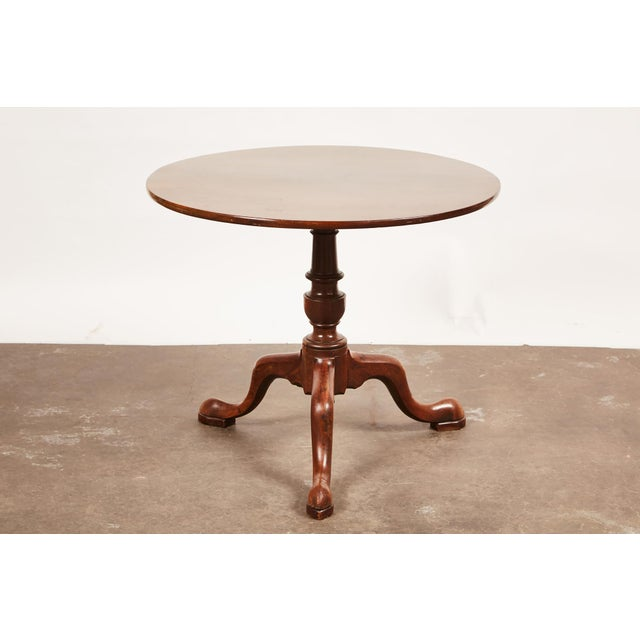 A 19th century English Queen Anne mahogany pedestal table on a tripod base featuring low snake feet.