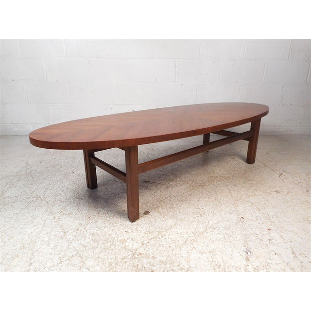 Stylish midcentury coffee table. Oval/surfboard tabletop with an interesting grain pattern, which is divided into four...