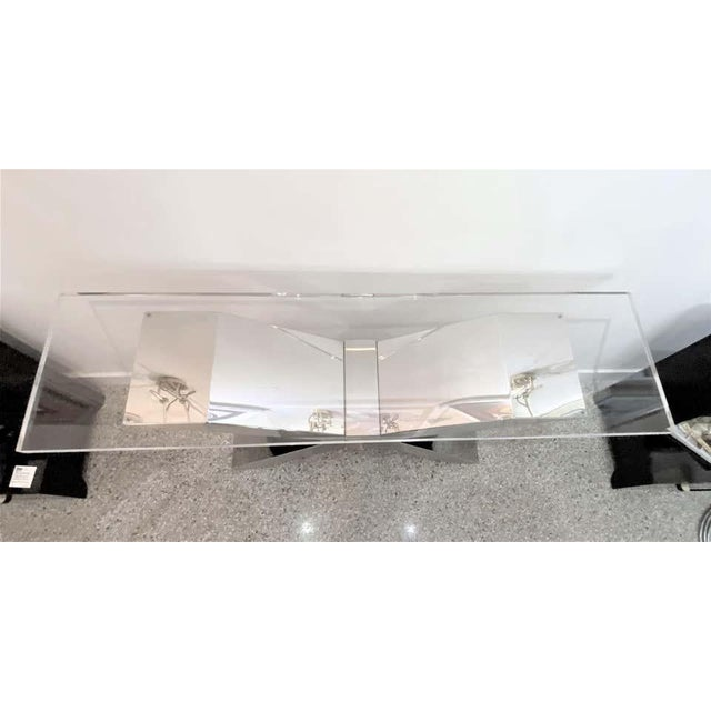 This stylish and bold X-form console table is fabricated in stainless steel and polished Lucite. The front and back of the...