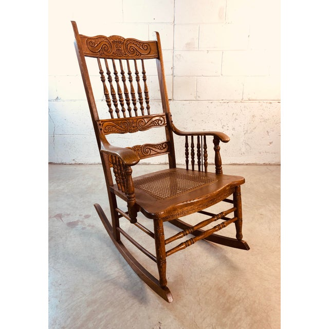 Quarter-Sawn oak hand carved rocking chair. The back of the chair is carved with a man blowing the wind. Similiar to Old...