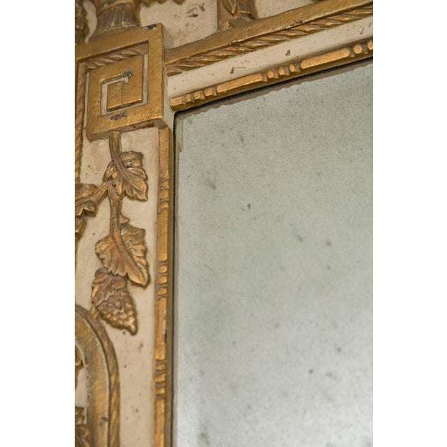 This Louis XVI style parcel-gilt and cream-painted mirror has a bevelled plate with a broken cartouche pediment centred by...