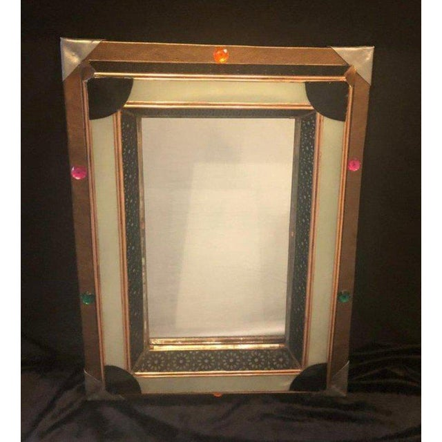 A delightful vanity or wall mirror featuring multicolored buttons and a faux leather frame. The mirror has a lighted milk...