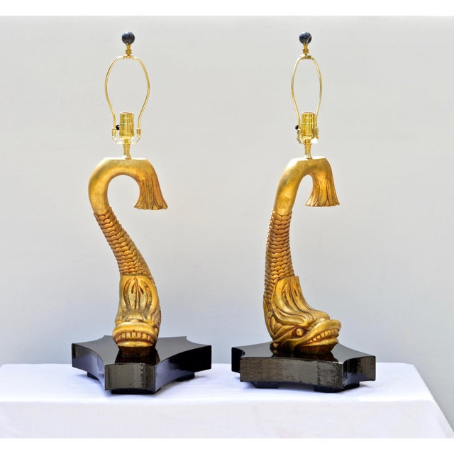 A stunning pair of gilt wood dolphins custom-mounted as table lamps. The curvy and sassy figural objects will add drama...