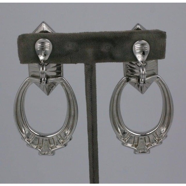 Silvertone jeweled earrings from Yves Saint Laurent with large stone and jewel decorated dangling hoops. Clip back...