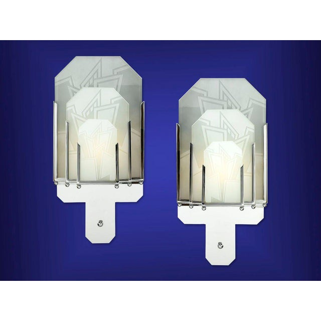 A superb pair of Art Deco sconces featuring panels of frosted glass, each exceptionally detailed. The geometric patterns...