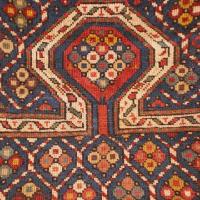 A 19th century Persian Kuba prayer carpet with central field of flowers on an indigo background, surrounded by several...