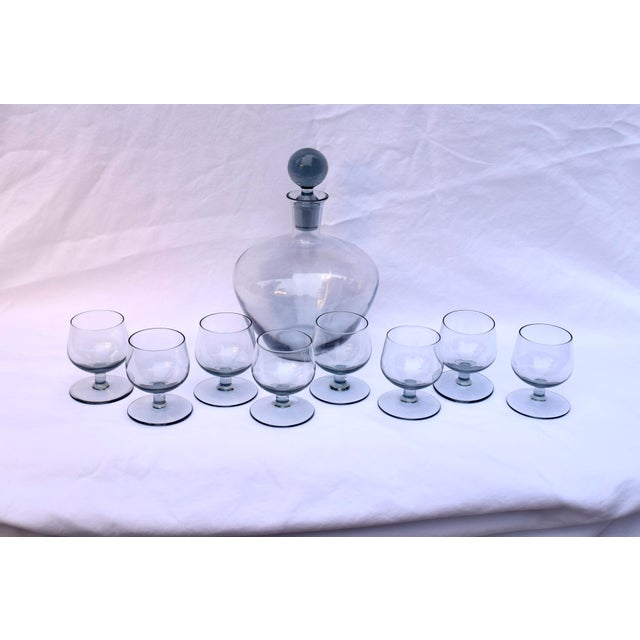 Mid-Century smoked glass cordial decanter set with 8 glasses. Etched # 45 on the bottom of the decanter. Glass height:...
