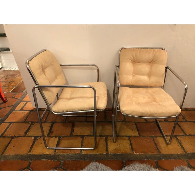 A sophisticated sleek pair of Milo Baughman Mid-Century Modern chrome and buck colored ultra- suede arm club chairs....