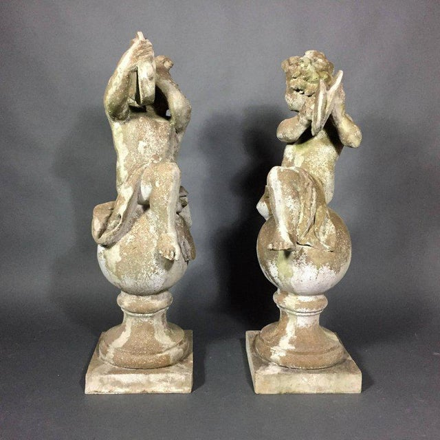 Pair of classic garden Puti playing delightfully on a ball finial over square base, each playing instruments, tamborine...