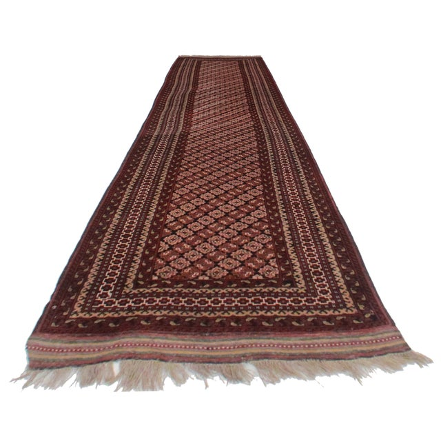 This is a vintage Persian Pakistani runner. Made of hand-knotted wool. It features a delicate, intricate all-over design.
