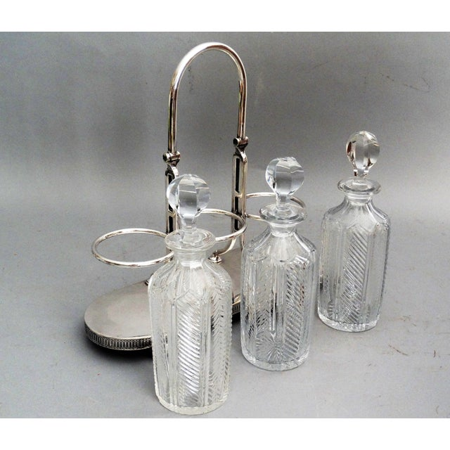 An English silver plate and cut-crystal 3 bottle liquor tantalus with a swing handle and ball feet. It has a decorative...