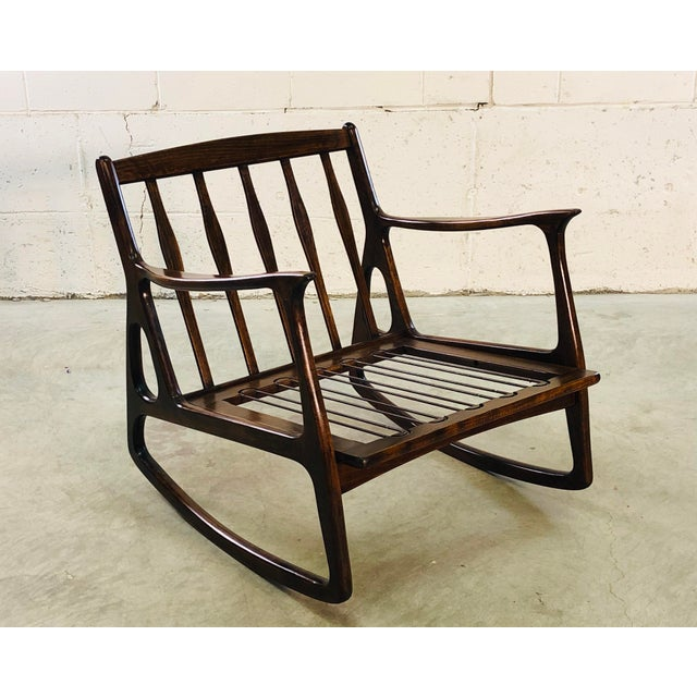 Vintage 1970s Italian dark beech wood rocking chair. The chair has thin, nicely designed arms and is in a dark wood...
