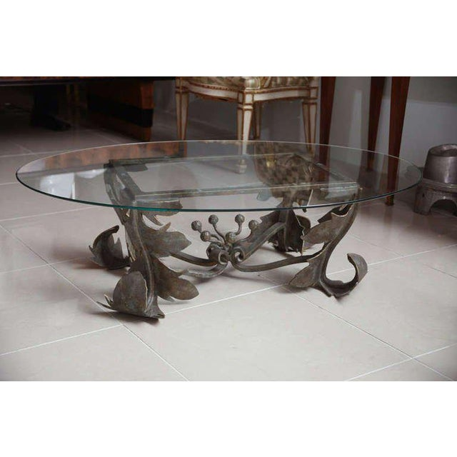 The oval glass top above a hand-forged bronze base with leaf tip decoration.