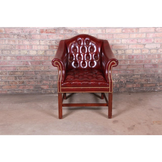 A gorgeous Chesterfield style club chair By Hancock & Moore USA, Circa 1980s Tufted burgundy leather with brass nailhead...