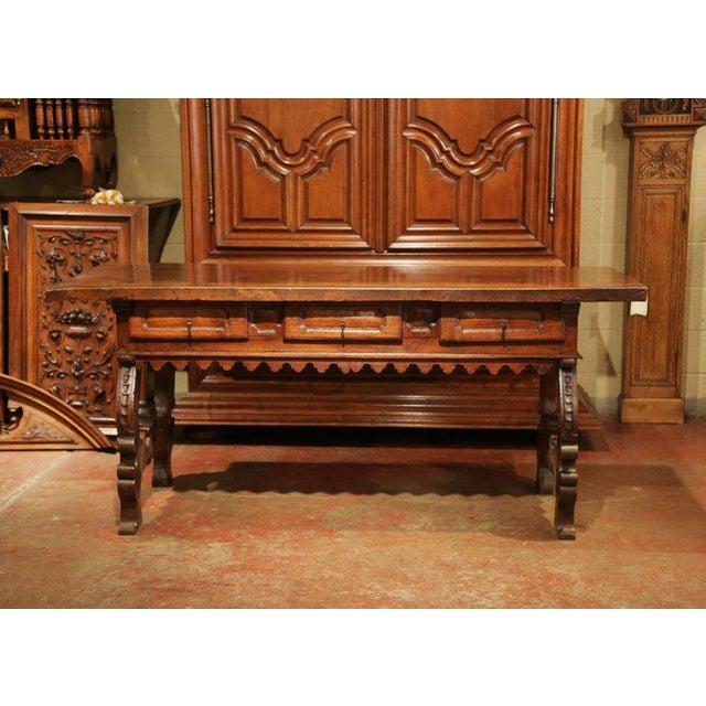 Carved in Spain, circa 1730, this antique console table flaunts an impressive Gothic style. The large, fruitwood desk has...