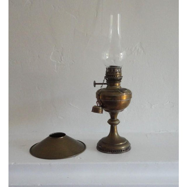 This fantastic early 19thc New England oil lamp has the original glass globe and wonderful brass shield. On the side of...