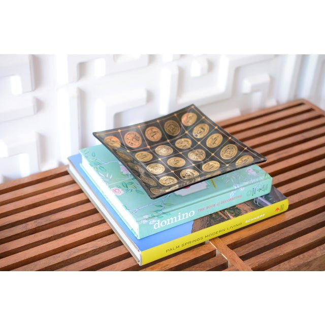 This listing is for a midcentury vintage, smoked glass catchall tray. It features shiny, gold coin medallion detailing....