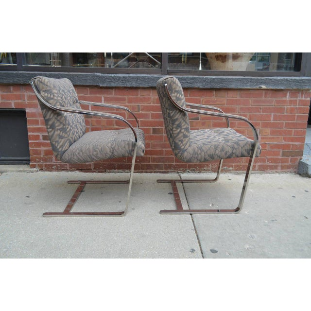 Eight finely crafted polished stainless steel and chrome dining chairs by Brueton. The chairs are cantilevered with...