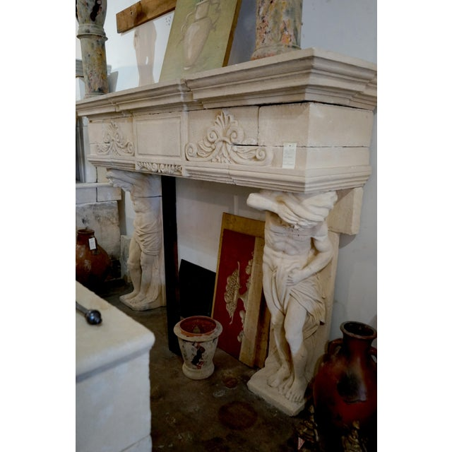 Monumental hand carved French limestone mantel supported by two finely detailed Atlas figures. Large rectangular cartouche...