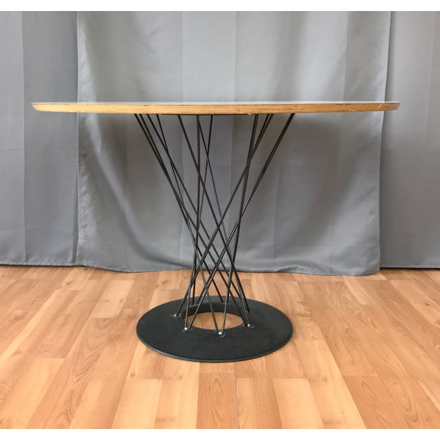 Modernica made circa 1990s cyclone dining table, first designed by Noguchi. Black wire set into a black steel base, white...