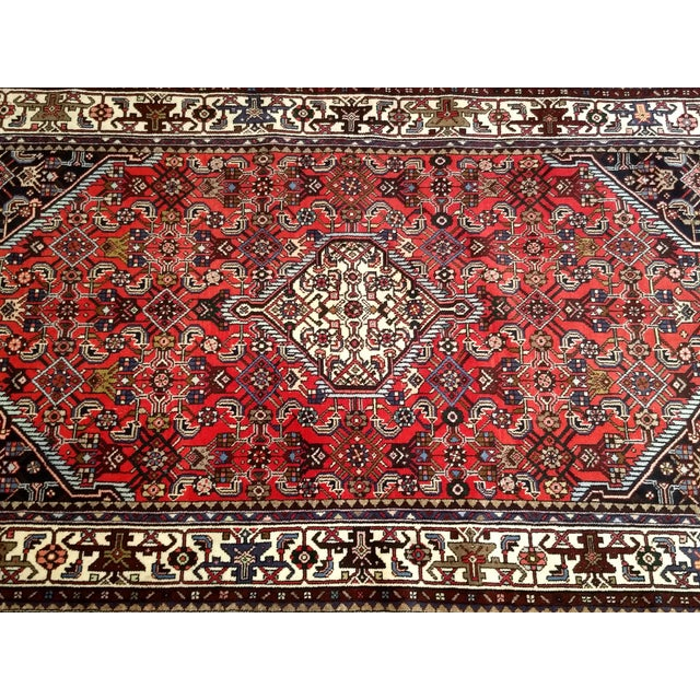 The small Hamadan area rug set in a red color field with Herati design and a central medallion in white color. The border...