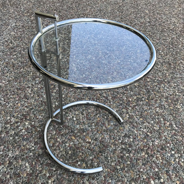 Iconic modern chrome & glass side table by Eileen Gray. The top height is adjustable with the metal pin.