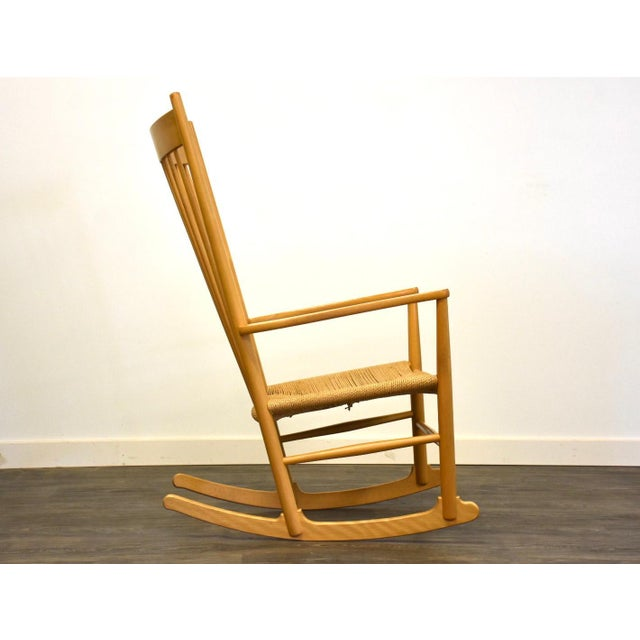 A mid-century modern J16 beechwood rocking chair designed by Hans J. Wegner for FDB Mobler. This rocker has a paper cord...