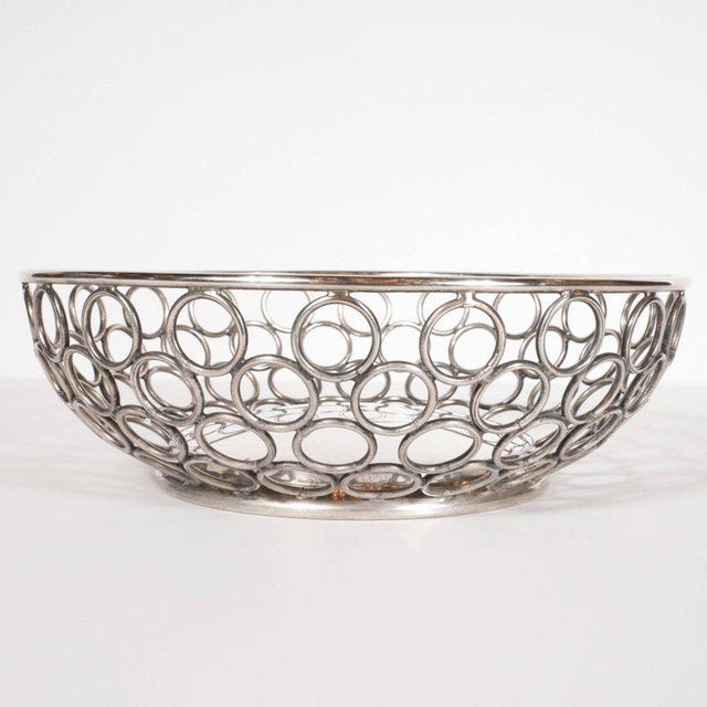 This Mid-Century Modern silver plate bowl or basket was realized in the United States by the renowned Massachussettes...