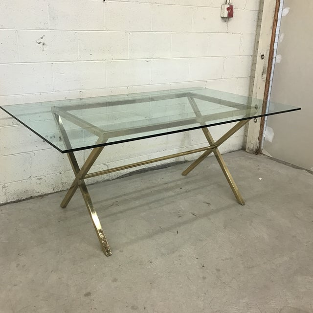 Classic brass X-base style with thick glass top. The brass is scuffed and patina'd. Reddish orange paint or scuffs are...
