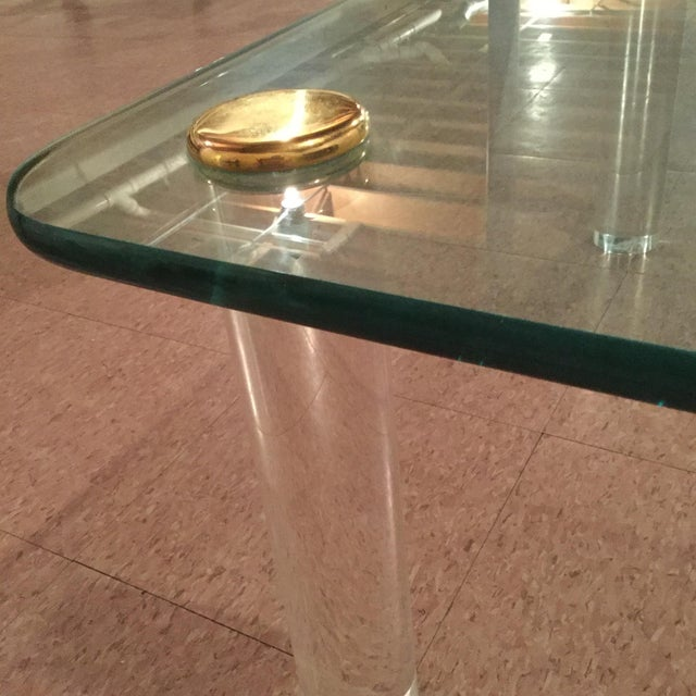 Unique, one-of-a-kind square glass table, thick, cylindrical, Lucite legs, fashioned with brass accents from the 1970s....