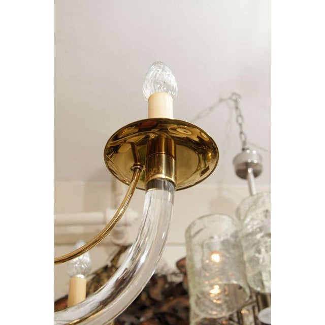 This chic chandelier was created in the 1970s. Its five arms and body are made from brass and Lucite and the materials...