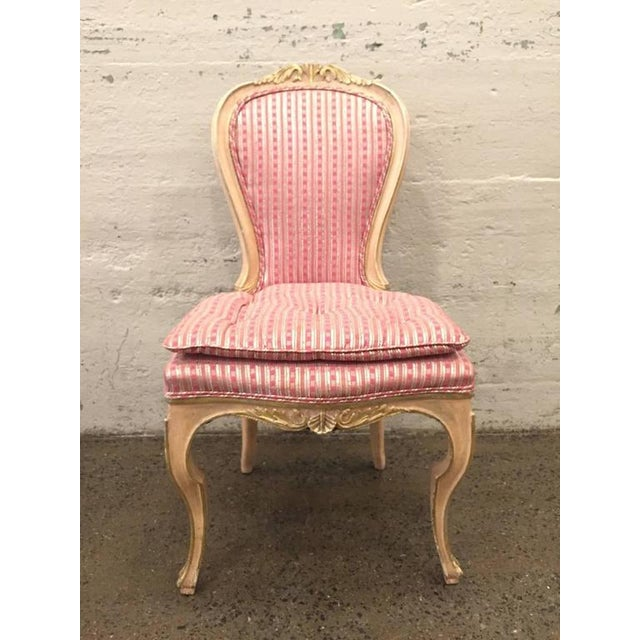 Set of eight Louis XVI style painted dining chairs. Painted with silver gilt trim to the carved wood frame. Has very...