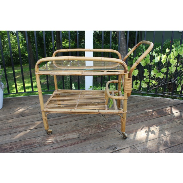 This vintage bamboo and rattan bar cart would be great for entertaining indoors or out in a covered area. It has 2 shelves...