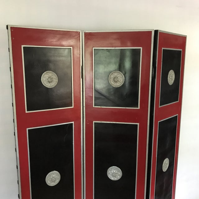 Vintage three panel wood room divider with lacquered panels and decorative rosettes.