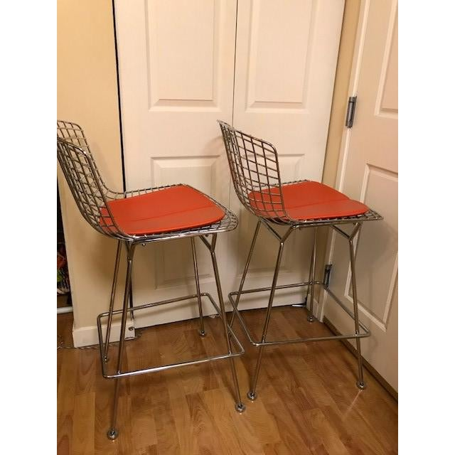 From Design Within Reach, pair (2) of chrome bar height stools with red vinyl chair pads made by Knoll for Bertoia....